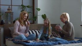 Χαρούμενη οικογένεια με τις κάρτες παιχνιδιού παιδιών στο κρεβάτι απόθεμα βίντεο