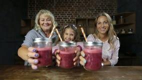 Χαρούμενη οικογένεια που πίνει το φρέσκο καταφερτζή μούρων απόθεμα βίντεο