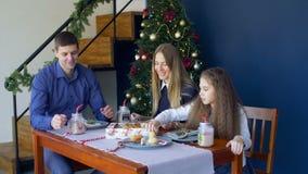 Χαρούμενη οικογένεια που τρώει τα μπισκότα Χριστουγέννων στην παραμονή Χριστουγέννων απόθεμα βίντεο