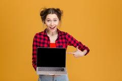 Χαρούμενη όμορφη εκμετάλλευση γυναικών και υπόδειξη στο κενό lap-top οθόνης Στοκ εικόνα με δικαίωμα ελεύθερης χρήσης