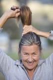 Χαρούμενη ώριμη τρίχα βουρτσίσματος γυναικών υπαίθρια Στοκ Εικόνες