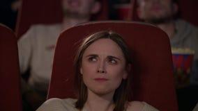 Χαρούμενοι άνθρωποι που προσέχουν τον κινηματογράφο στον κινηματογράφο και που τρώνε popcorn απόθεμα βίντεο