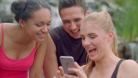 Χαρούμενοι άνθρωποι που χρησιμοποιούν το τηλέφωνο υπαίθριο Εύθυμοι φίλοι που προσέχουν τις φωτογραφίες στο τηλέφωνο φιλμ μικρού μήκους