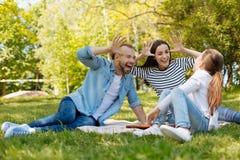 Χαρούμενοι γονείς που κάνουν τα πρόσωπα για την κόρη τους Στοκ εικόνες με δικαίωμα ελεύθερης χρήσης