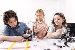 Χαρούμενοι μικροί φίλοι που εργάζονται στο πρόγραμμα τεχνολογίας στο σχολείο Στοκ Εικόνα