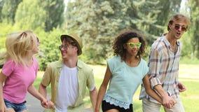 Χαρούμενοι νέοι που γελούν, που χορεύουν και που πηδούν υψηλοί κρατώντας τα χέρια τους απόθεμα βίντεο