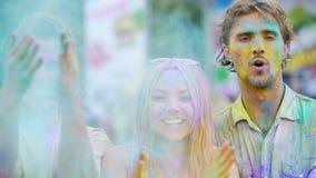 Χαρούμενοι νέοι που χαμογελούν στη κάμερα, που χτυπά τα χέρια που καλύπτονται στη σκόνη χρώματος απόθεμα βίντεο