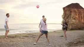 Χαρούμενοι νέοι φίλοι που παίζουν volley τη σφαίρα στην παραλία θαλασσίως το βράδυ ενεργές διακοπές Σε αργή κίνηση πυροβολισμός απόθεμα βίντεο