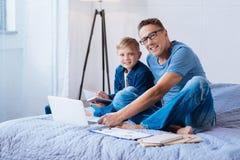 Χαρούμενοι πατέρας και γιος που θέτουν μελετώντας από κοινού Στοκ εικόνες με δικαίωμα ελεύθερης χρήσης
