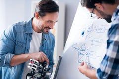Χαρούμενοι συνάδελφοι που σύρουν το σχέδιο Στοκ Φωτογραφία