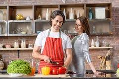 Χαρούμενοι σύζυγος και σύζυγος που προετοιμάζουν τα τρόφιμα στην κουζίνα στοκ εικόνες