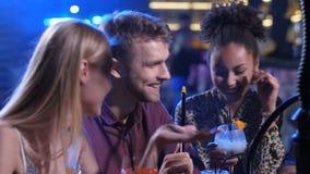 Χαρούμενοι φίλοι που έχουν τη διασκέδαση στο φραγμό disco με το hookah απόθεμα βίντεο