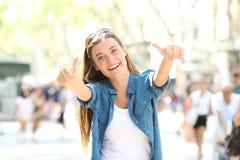 Χαρούμενοι gesturing αντίχειρες κοριτσιών επάνω στην οδό στοκ φωτογραφίες