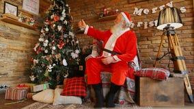 Χαρούμενος Άγιος Βασίλης συλλαμβάνει το χριστουγεννιάτικο δέντρο απόθεμα βίντεο