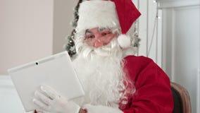 Χαρούμενος Άγιος Βασίλης που ελέγχει επάνω τα ηλεκτρονικά ταχυδρομεία Χριστουγέννων από τα παιδιά στην ψηφιακή ταμπλέτα του απόθεμα βίντεο