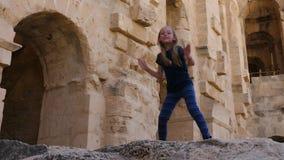 Χαρούμενος έφηβος κοριτσιών που χορεύει στους πετρώδεις τοίχους υποβάθρου στο αρχαίο φρούριο απόθεμα βίντεο