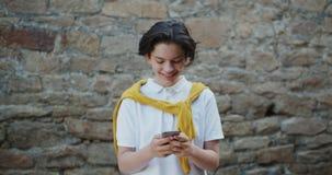 Χαρούμενος έφηβος που χρησιμοποιεί το smartphone στην οδό που χαμογελά έχοντας τη διασκέδαση με τη συσκευή απόθεμα βίντεο