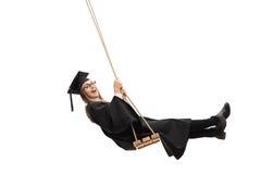 Χαρούμενος απόφοιτος φοιτητής που ταλαντεύεται σε μια ταλάντευση Στοκ Εικόνα