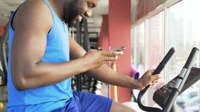 Χαρούμενος αρσενικός αθλητής που οδηγά το στάσιμο ποδήλατο και που απαντά στο τηλεφωνικό μήνυμα στη γυμναστική φιλμ μικρού μήκους