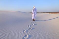Χαρούμενος αρσενικός μουσουλμάνος περπατά μέσω της άσπρης ερήμου άμμου και απολαμβάνει το λι Στοκ Εικόνες