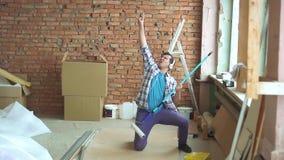 Χαρούμενος αρσενικός οικοδόμος στα παιχνίδια πουκάμισων σε μια φανταστική κιθάρα κατά τη διάρκεια της επισκευής απόθεμα βίντεο