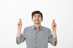 Χαρούμενος ελκυστικός γενειοφόρος τύπος ελπίδας στο ριγωτό πουκάμισο, ανατρέχοντας διασχίζοντας τα δάχτυλα και κάνοντας με ή προσ Στοκ φωτογραφίες με δικαίωμα ελεύθερης χρήσης