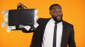 Χαρούμενος επιχειρηματίας αφροαμερικάνων που παρουσιάζει τσάντα με τα μετρητά δολαρίων, εισόδημα απόθεμα βίντεο