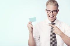 Χαρούμενος επιχειρηματίας που δείχνει το δάχτυλο στην κενή κάρτα. Στοκ Εικόνες