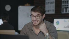 Χαρούμενος επιχειρηματίας που εξετάζει την οθόνη lap-top και που κάνει ναι τη χειρονομία στο σκοτεινό γραφείο απόθεμα βίντεο