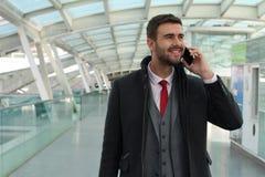 Χαρούμενος επιχειρηματίας που καλεί τηλεφωνικώς από το σταθμό τρένου Στοκ εικόνες με δικαίωμα ελεύθερης χρήσης