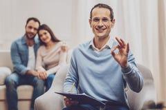 Χαρούμενος ευχαριστημένος ψυχολόγος που παρουσιάζει ΕΝΤΑΞΕΙ σημάδι στοκ φωτογραφία