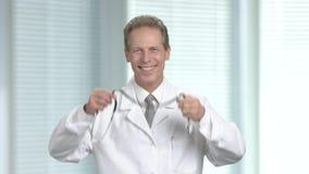 Χαρούμενος καρδιολόγος που παρουσιάζει αντίχειρα φιλμ μικρού μήκους