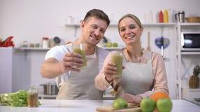 Χαρούμενος καταφερτζής spirulina εκμετάλλευσης ζευγών, που συστήνει το υγιές ποτό, βιταμίνες απόθεμα βίντεο