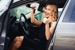 Χαρούμενος ξανθός στο αυτοκίνητο, που κρατά τα κλειδιά και που παρουσιάζει αντίχειρα Στοκ Εικόνες