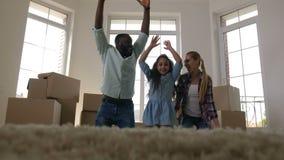 Χαρούμενος οικογενειακός κυλώντας τάπητας στο πάτωμα στο καινούργιο σπίτι απόθεμα βίντεο