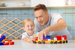 Χαρούμενος πατέρας της Νίκαιας που εξετάζει το τραίνο παιχνιδιών Στοκ φωτογραφίες με δικαίωμα ελεύθερης χρήσης