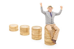 Χαρούμενος πρεσβύτερος που κάθεται σε έναν σωρό των νομισμάτων Στοκ εικόνα με δικαίωμα ελεύθερης χρήσης