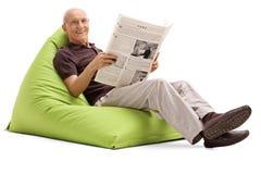 Χαρούμενος πρεσβύτερος που κρατά μια εφημερίδα στοκ εικόνα