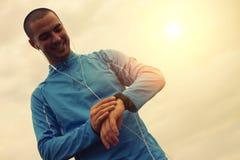 Χαρούμενος δρομέας που εξετάζει το έξυπνο ρολόι Εστίαση στο πρόσωπο στοκ φωτογραφία με δικαίωμα ελεύθερης χρήσης