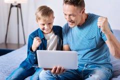 Χαρούμενος στόχος εορτασμού πατέρων και γιων προσέχοντας το ποδόσφαιρο on-line Στοκ Φωτογραφίες