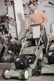 Χαρούμενος τύπος που αποφασίζει σχετικά με τον καλύτερο χορτοκόπτη στο κατάστημα εξοπλισμού κήπων Στοκ φωτογραφίες με δικαίωμα ελεύθερης χρήσης