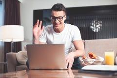 Χαρούμενος τύπος που χρησιμοποιεί τον υπολογιστή για τη σε απευθείας σύνδεση επικοινωνία στοκ φωτογραφία με δικαίωμα ελεύθερης χρήσης