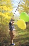 Χαρούμενο αγόρι με τα μπαλόνια στο πάρκο φθινοπώρου Στοκ Εικόνα