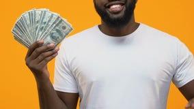 Χαρούμενο αφρικανικό αρσενικό που δείχνει τους λογαριασμούς δολαρίων διαθέσιμους, την οικονομική επιτυχία, επένδυση απόθεμα βίντεο