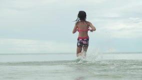 Χαρούμενο ευτυχές νέο κορίτσι που τρέχει στο σε αργή κίνηση βίντεο μήκους σε πόδηα αποθεμάτων ψεκασμού θάλασσας νερού φιλμ μικρού μήκους