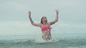 Χαρούμενο ευτυχές παιχνίδι νέων κοριτσιών με το ράντισμα του νερού στο σε αργή κίνηση βίντεο μήκους σε πόδηα αποθεμάτων θάλασσας απόθεμα βίντεο