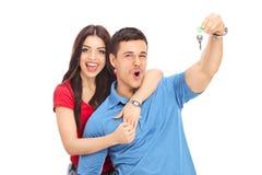 Χαρούμενο ζεύγος που κρατά μια βασική και gesturing ευτυχία Στοκ φωτογραφία με δικαίωμα ελεύθερης χρήσης