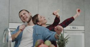 Χαρούμενο ζεύγος στη σύγχρονη κουζίνα πρίν αρχίζει να μαγειρεύεται το πρόγευμα αυτοί που τραγουδούν και που χορεύουν αστείοι από  απόθεμα βίντεο