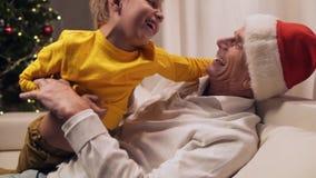 Χαρούμενο ηλικίας άτομο που στηρίζεται με τον εγγονό του στο σπίτι απόθεμα βίντεο