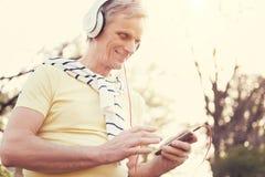 Χαρούμενο ηλικιωμένο άτομο που χρησιμοποιεί έναν MP3 φορέα Στοκ Φωτογραφία
